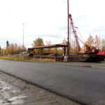 picture of real estate commercial land on olive road in Anchorage Alaska. Old equipment with rust in picture.