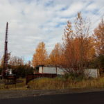 picture of real estate commercial land on olive road in Anchorage Alaska. Yellow trees in fall. Some old trailers in picture.